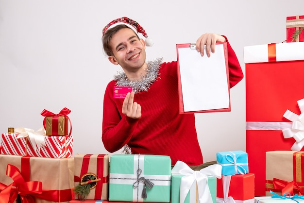 Front view rejoiced young man holding clipboard and card sitting around xmas gifts
