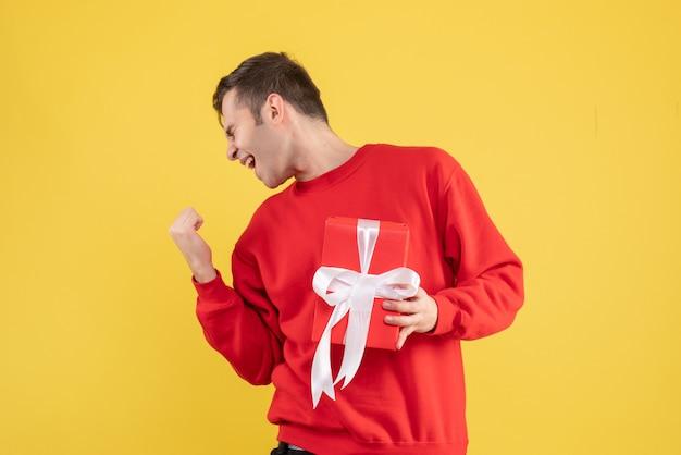 正面図は黄色の上に立っている赤いセーターで若い男を喜んだ
