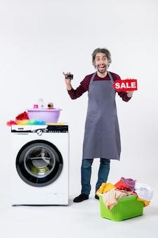 전면 보기는 흰 벽에 있는 세탁기 세탁 바구니 근처에 서 있는 카드와 판매 표지판을 들고 기뻐한 청년