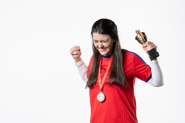 Вид спереди радующегося игрока-женщины в спортивной одежде с медалью и золотым кубком