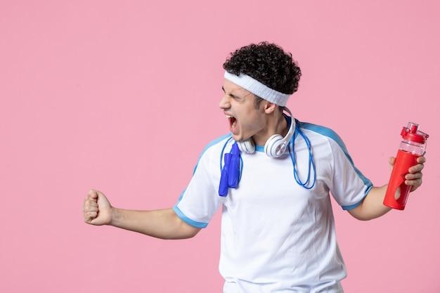 Вид спереди ликуя спортсмена в спортивной одежде с бутылкой воды