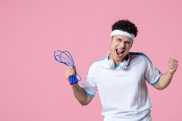 縄跳びでスポーツ服を着た若い男性を喜ぶ正面図