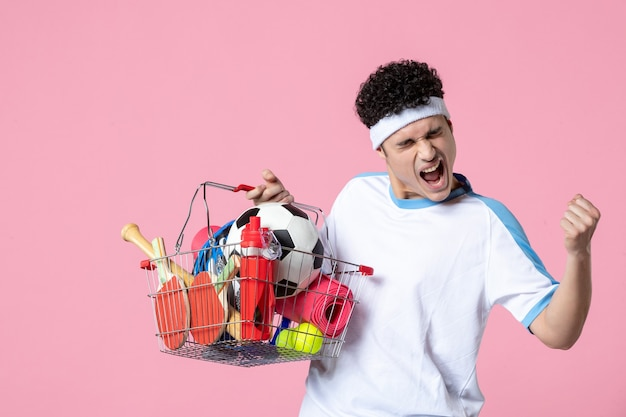 Front view rejoicing young male in sport clothes with basket full of sport things