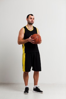Front view of relaxed basketball player posing with ball