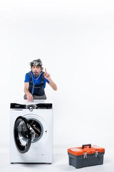 Vista frontale del riparatore con la lampada frontale che mette lo stetoscopio sulla lavatrice sulla parete bianca