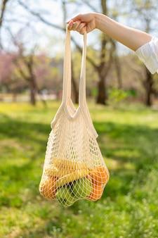 La borsa riutilizzabile di vista frontale ha tenuto dalla mano della donna in natura