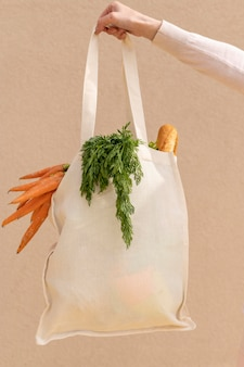Front view reusable bag with groceries held by woman hand