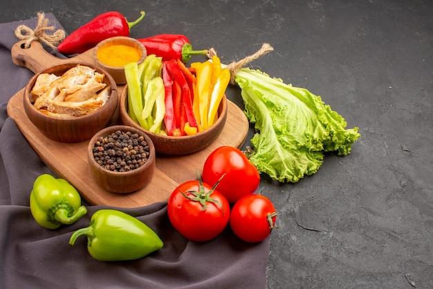 暗い空間に調味料を入れた熟した新鮮な野菜の正面図