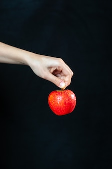 Front view ripe red apple in hand on dark surface