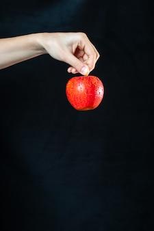 Вид спереди спелое красное яблоко в руке на темной поверхности