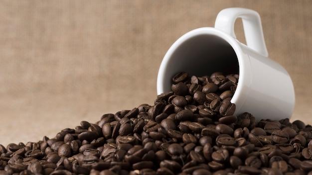 Вид спереди жареных кофейных зерен пролитой из белой кружки