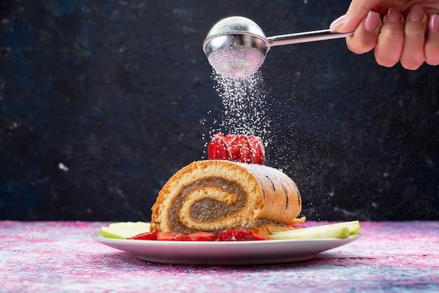 Torta di rotolo di vista frontale con frutta all'interno del piatto bianco