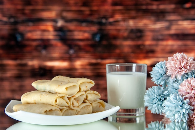 Front view rolled sweet pancakes with glass of milk on brown background meal cake breakfast food flower color morning pie sugar