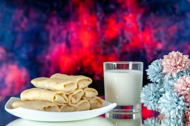 Front view rolled sweet pancakes with glass of milk on dark background meal breakfast food flower color cake morning pie