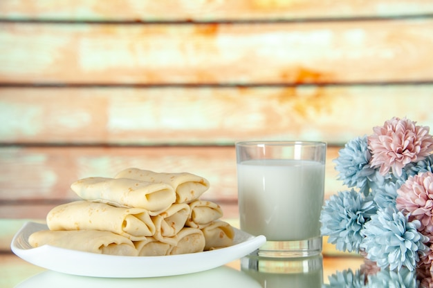 Front view rolled sweet pancakes with glass of milk on a light background meal cake breakfast food flower color morning pie sugar