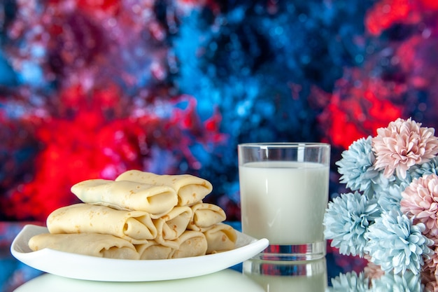 Front view rolled sweet pancakes with glass of milk on red blue background meal breakfast food sugar flower color cake morning pie