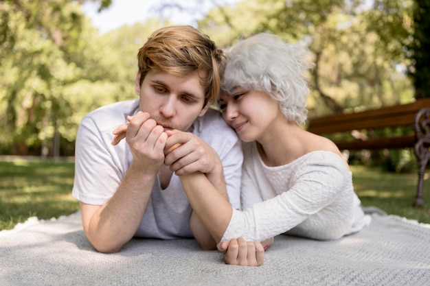 Front view of romantic couple outdoors on a blanket