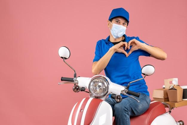 Vista frontale dell'uomo romantico del corriere in maschera medica che indossa un cappello seduto su uno scooter che consegna ordini facendo un gesto del cuore su sfondo color pesca pastello