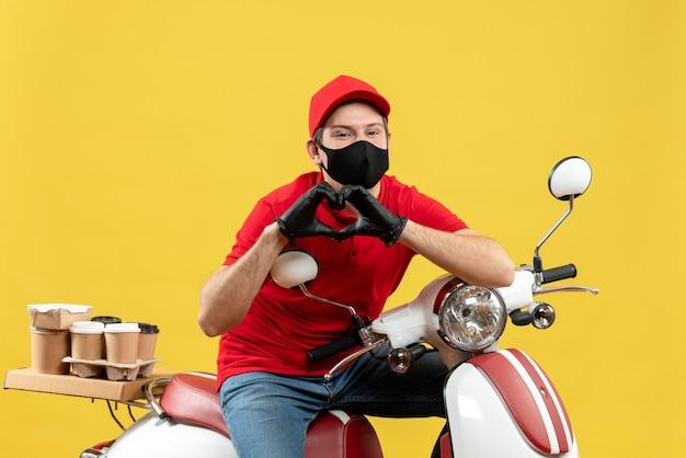 Vista frontale del corriere romantico uomo che indossa guanti rossi camicetta e cappello in mascherina medica consegna ordine seduto su scooter che fa gesto di cuore