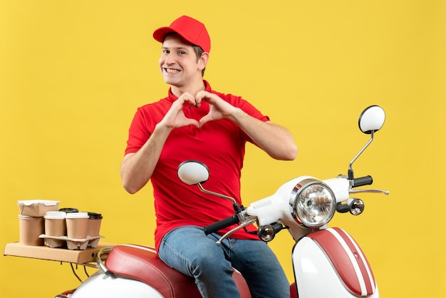 Front view of romantic young guy wearing red blouse and hat delivering orders making heart gesture on yellow background