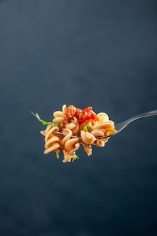 Front view rotini pasta on fork on dark isolated surface free space
