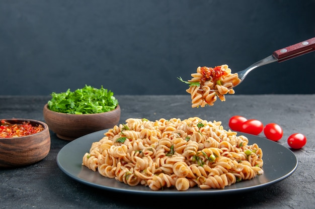Front view rotini pasta on plate and on fork chopped greens in bowl cherry tomatoes on dark isolated surface