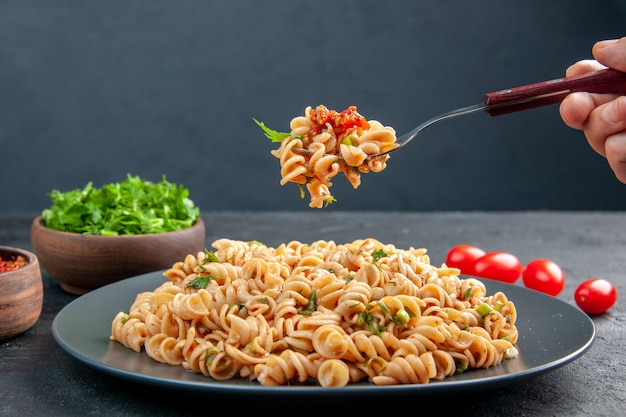 Front view rotini pasta on plate fork in female hand chopped greens in bowl cherry tomatoes on grey surface