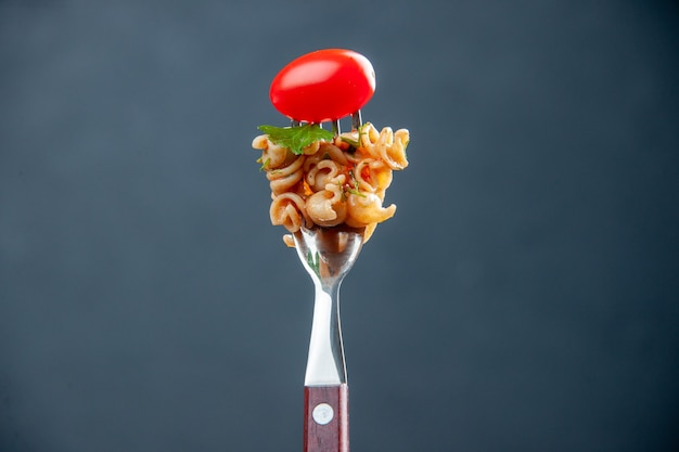 Front view rotini pasta with cherry tomato on fork on grey isolated surface with free space