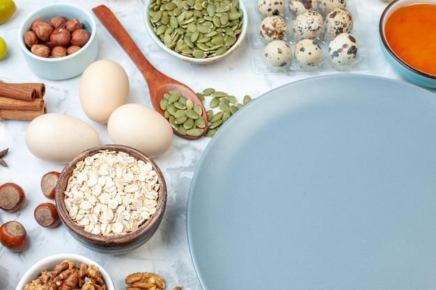 正面図小麦粉ゼリー卵と白い背景の上のさまざまなナッツと丸い青いプレート砂糖生地フルーツ写真パイナッツ甘いケーキ