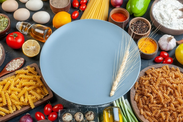 Front view round blue plate with raw pasta flour vegetables seasonings ands on dark