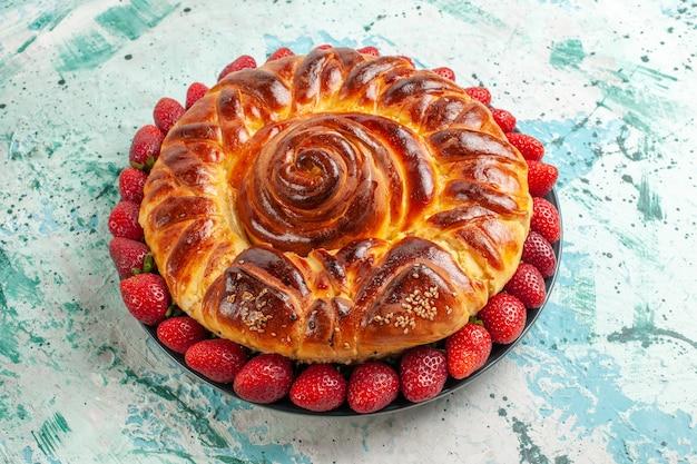 Vista frontale rotonda deliziosa torta con fragole rosse fresche sulla superficie azzurra torta pasticceria pasta zucchero biscotto dolce