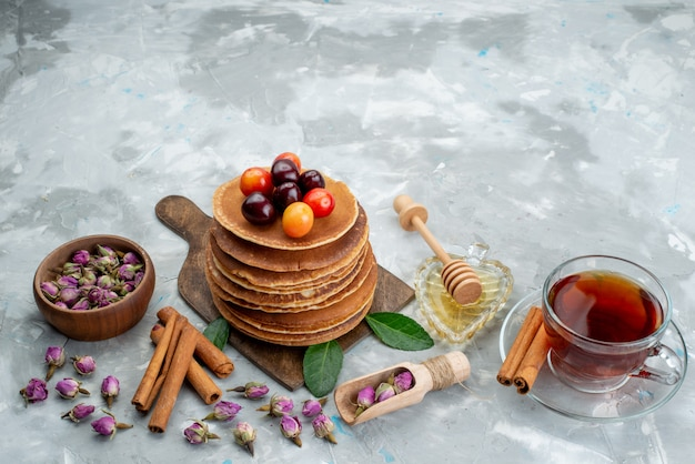 A front view round pancakes baked and delicious with cherries tea and cinnamon on the light desk cake fruit