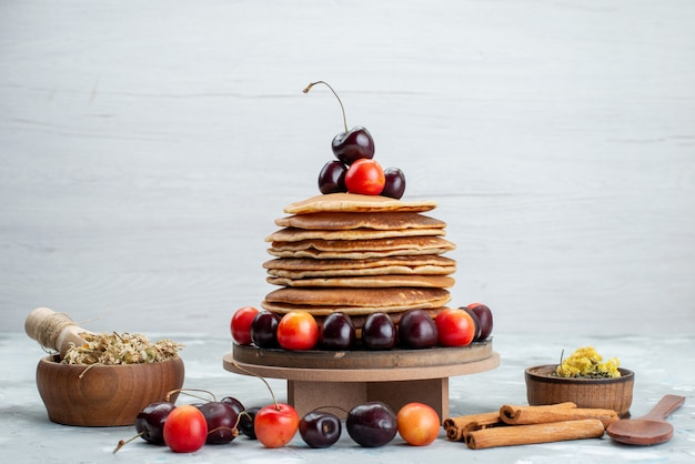 A front view round pancakes with cherries and cinnamon on the light desk cake fruit