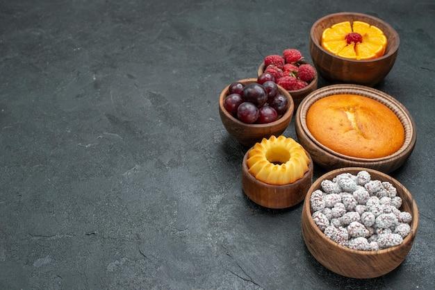 ダークグレーの背景にフルーツとキャンディーの正面図丸いパイ甘いビスケットフルーツパイケーキベリー