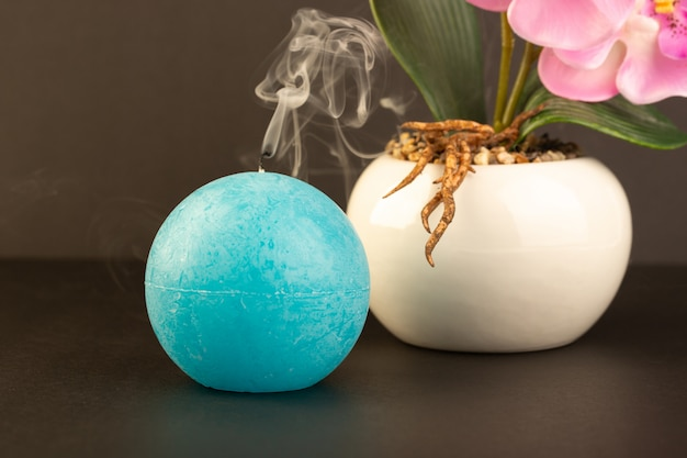 A front view round shaped candle blew out blue colored designed along with potty with flower on the dark background bright fire decoration