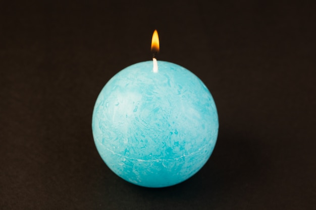 A front view round shaped candle lighting blue colored designed on the dark background bright fire decoration