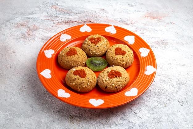 Biscotti di zucchero rotondi di vista frontale all'interno del piatto sulla torta dolce dello zucchero del biscotto del biscotto di superficie bianca