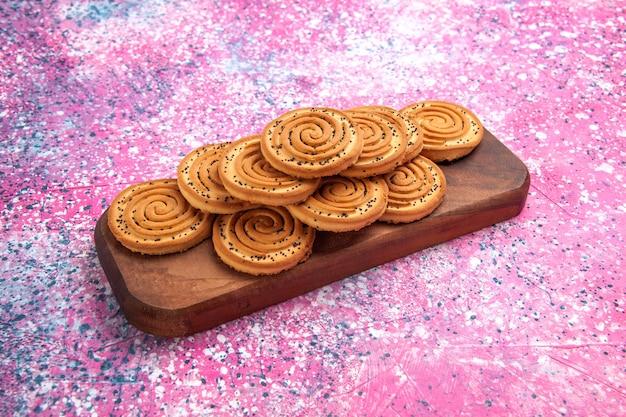 ピンクの背景に並ぶ甘いクッキーの正面図。
