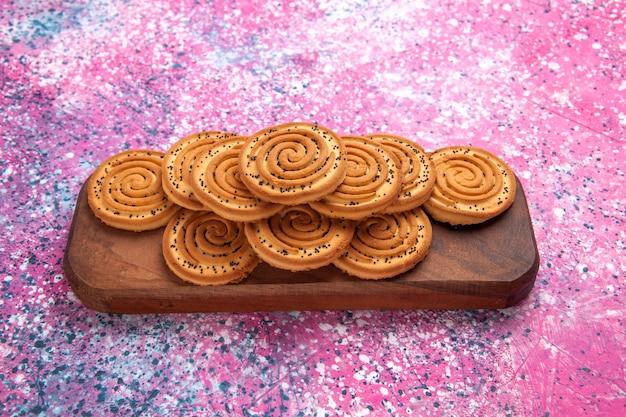 Biscotti dolci rotondi di vista frontale allineati sulla scrivania rosa.