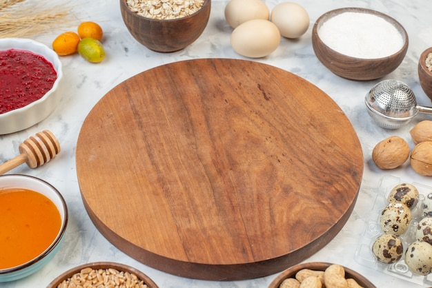 Front view of round wooden board among flour jam honey eggs brown rice on ice background