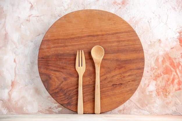 Vista frontale del tagliere rotondo in legno e dei cucchiai in piedi su una superficie colorata