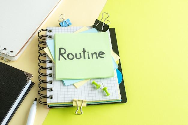 Nota scritta di routine vista frontale su adesivi con blocchi per appunti su sfondo giallo-verde