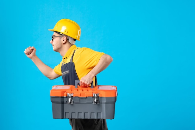Front view of running male builder in uniform with tool box in his hands on a blue