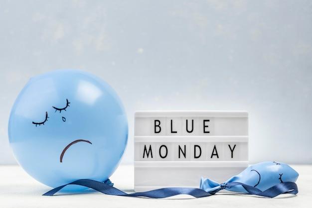 Vista frontale del palloncino triste con scatola luminosa per lunedì blu