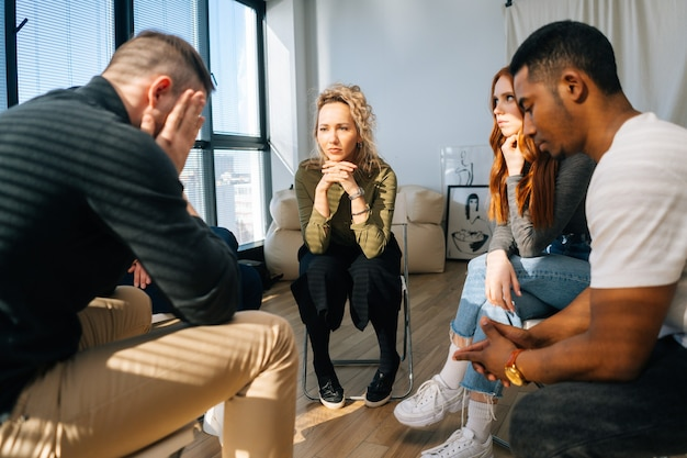 Front view of sad desperate young man telling sad story of mental problem or addiction to other patients sitting in circle during group interpersonal therapy session.