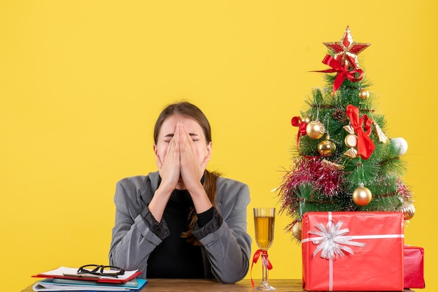 소리와 손 크리스마스 트리와 선물 칵테일로 그녀의 얼굴을 덮고 책상에 앉아 전면보기 슬픈 소녀