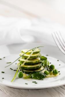 Салат из огурцов на белой тарелке, вид спереди