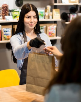 Front view sales assistant handing out groceries bag