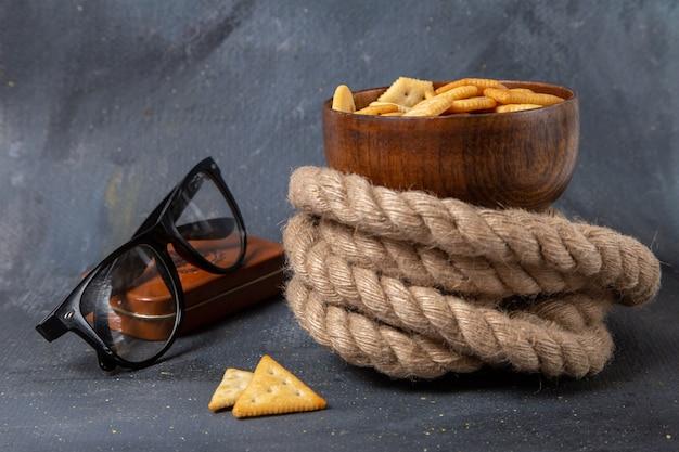 Соленые крекеры, вид спереди, внутри коричневой тарелки с солнцезащитными очками и веревками на сером