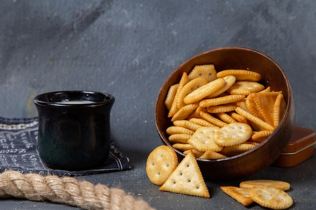 Front view salted crackers with cup of milk on grey